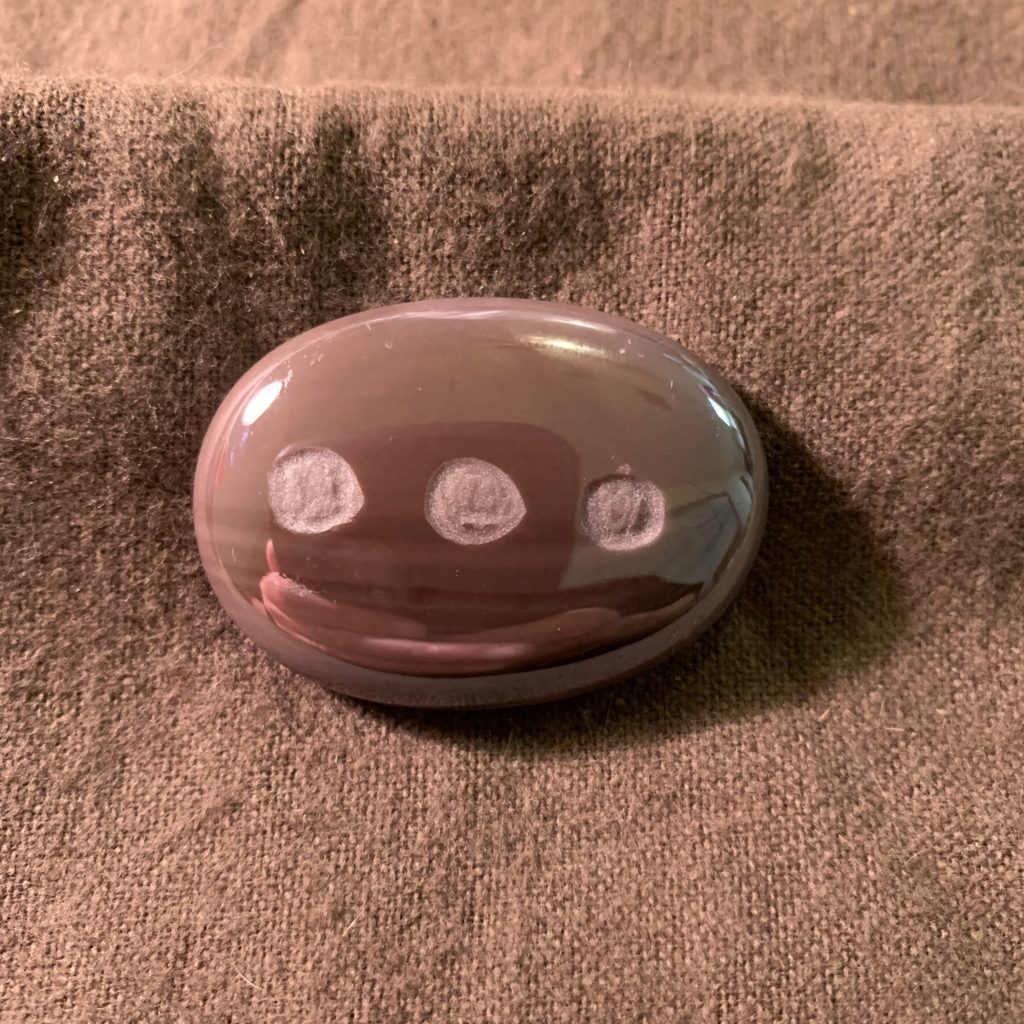Purple oval MyRockAndI worry stone with Elipses (Dot dot dots) engraved on it