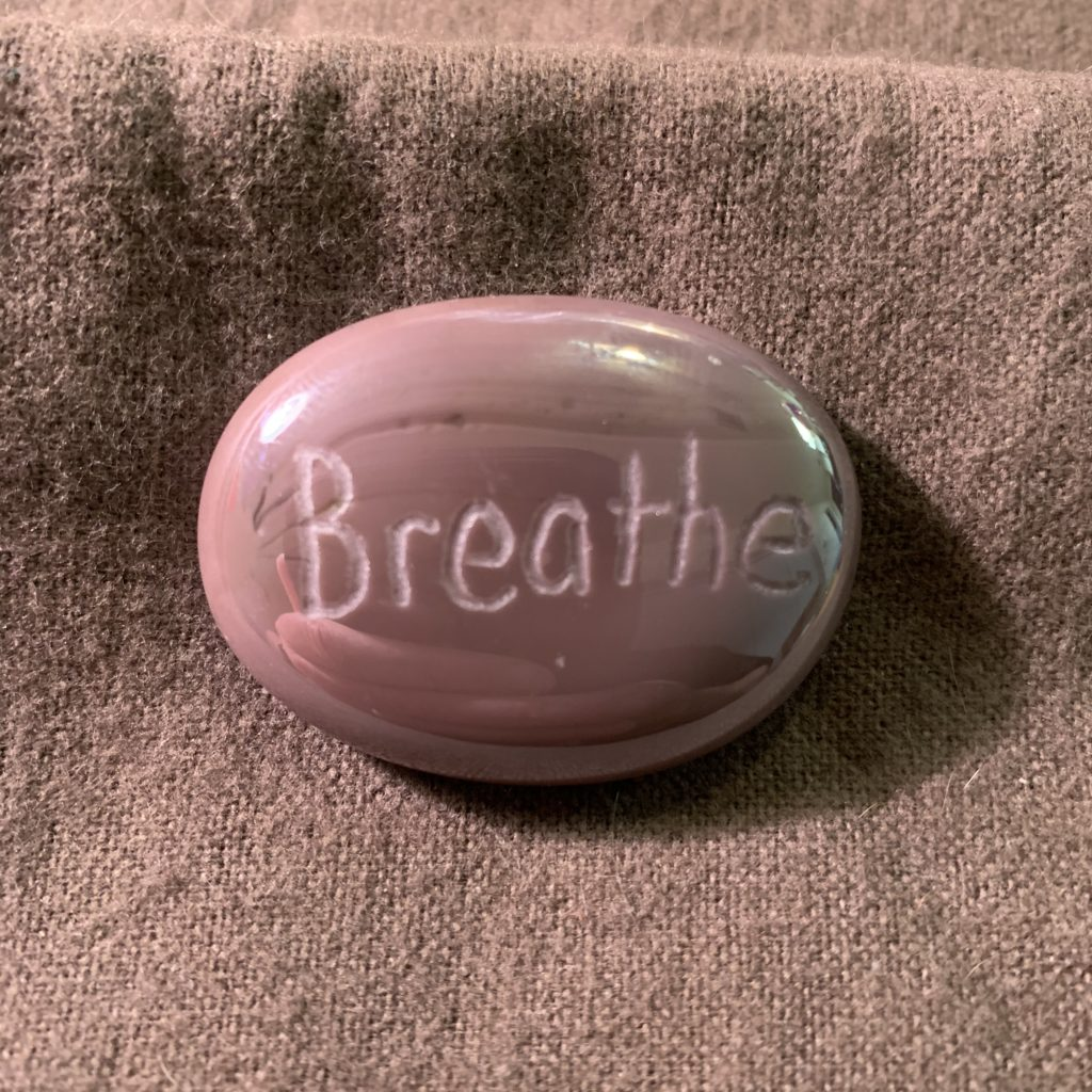 Purple oval MyRockAndI worry stone with Breathe engraved on it